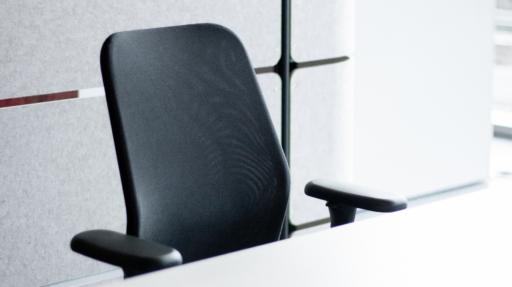 Zwarte bureaustoel aan witte bureau