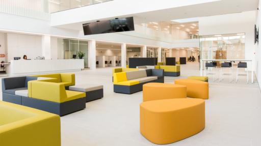 Ontvangstruimte met gele en grijze zetels